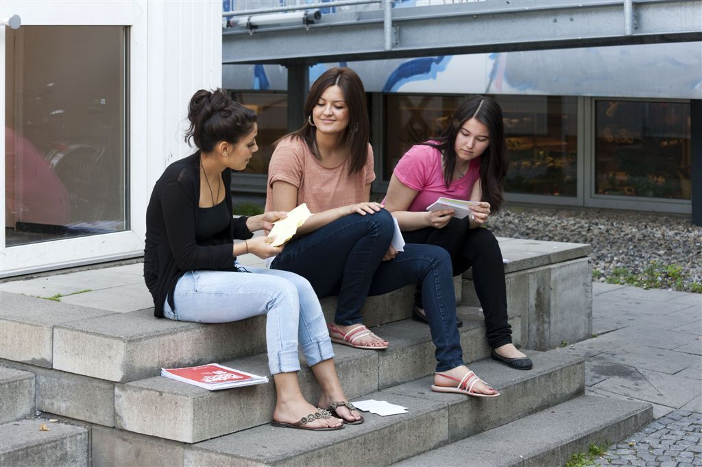 Three female students sitting on steps