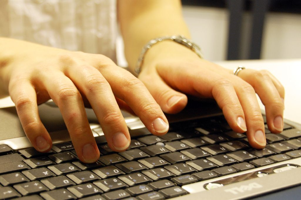 Woman types on a computer keyboard