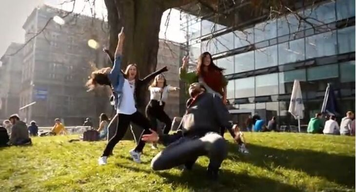 Students dancing on grass in front of the SuperC