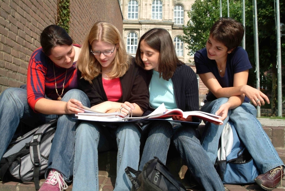Female students sit on steps looking at book
