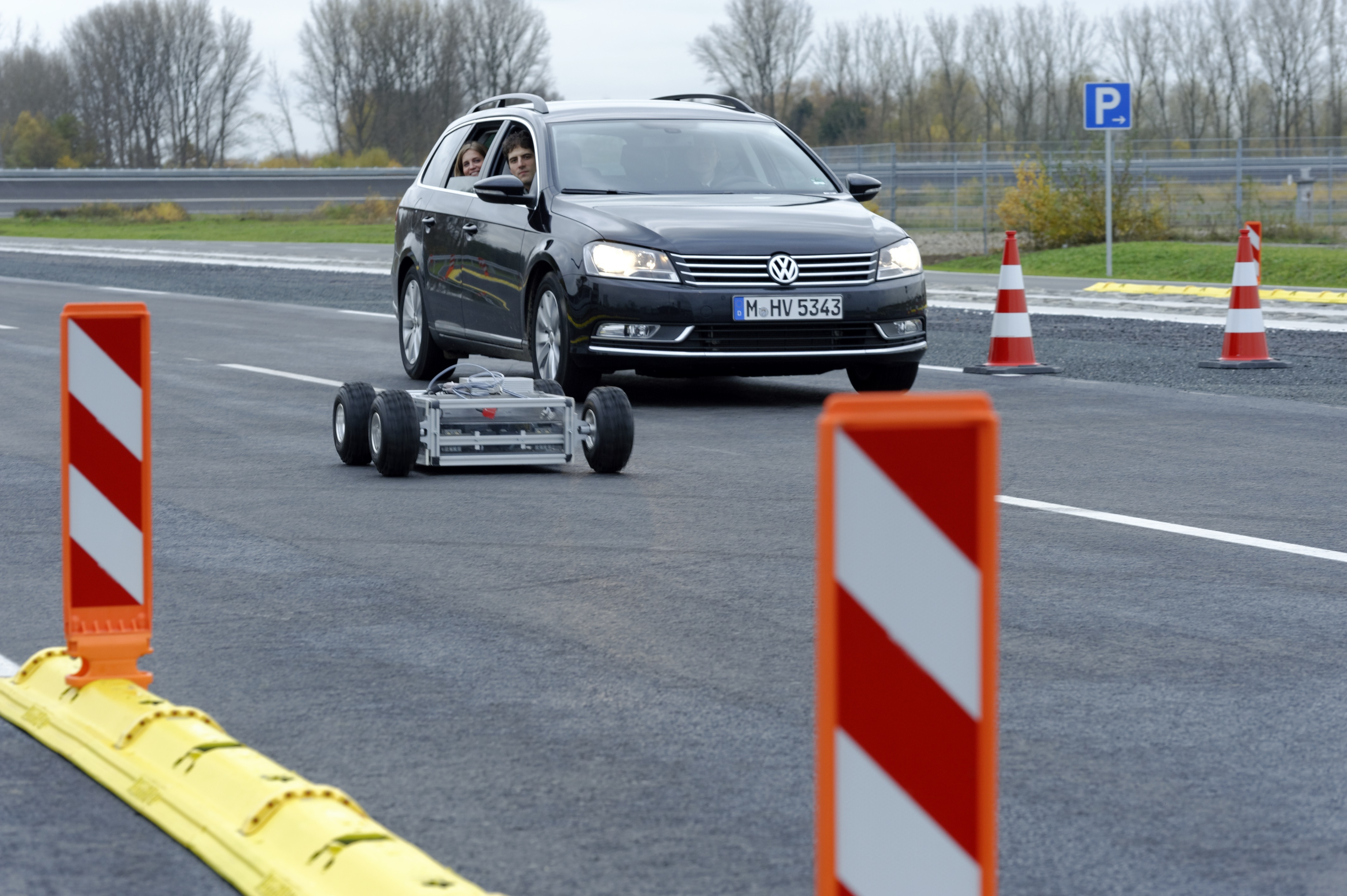 The satellite-guided IRT buggy is controlled by the passenger of the car, which is following the buggy in its background.
