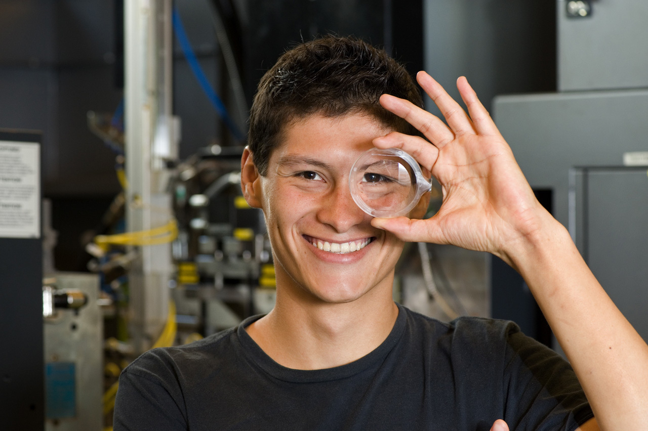 A young scientist looking through a lense