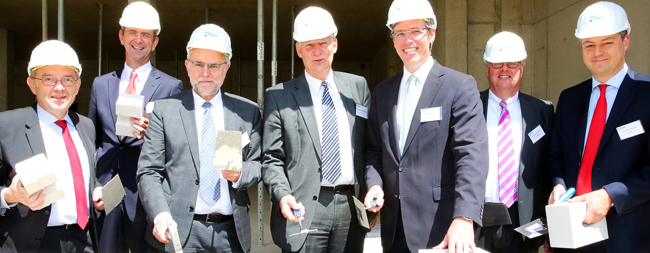 Representatives from the City, the University, and the investor company celebrate progress at the building site.