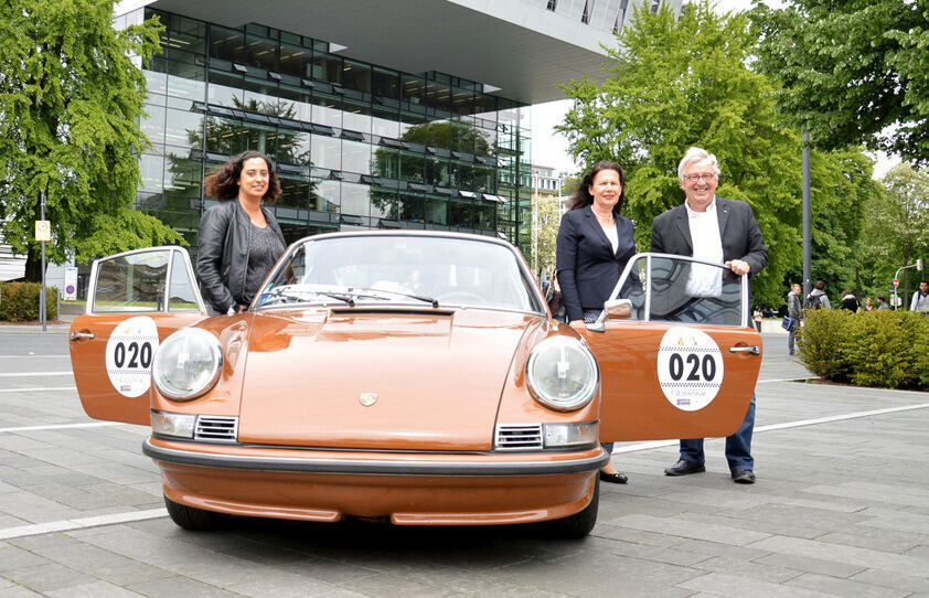 Ramona Böing, Prof. Doris Klee and Hans Keller in front of a brown Porsche from the seventies