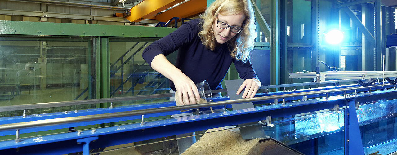 Female researcher in front of a model of a dam