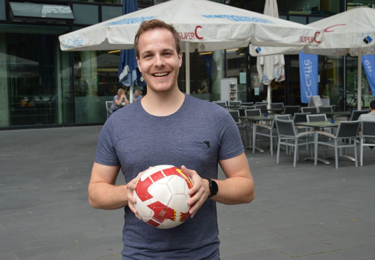 Man in front of SuperC with football in hands