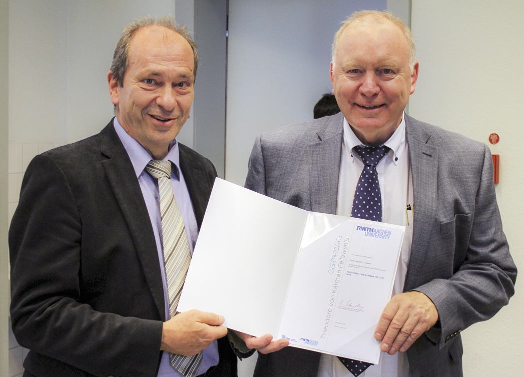 Prof Mayer hands over a certifcate to Prof Fraser