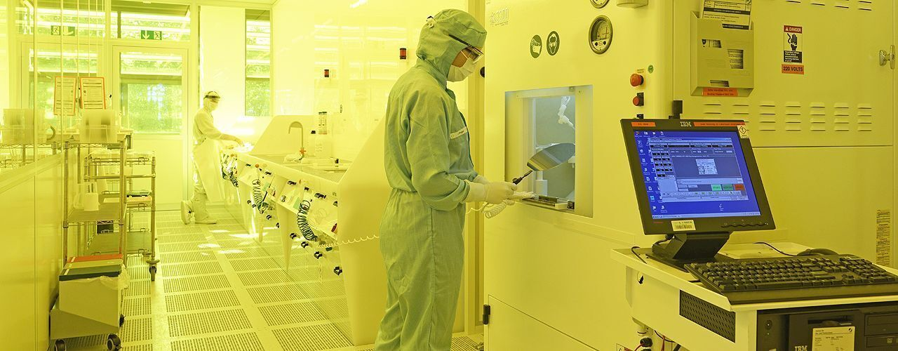 Researchers in protective suits in a cleanroom