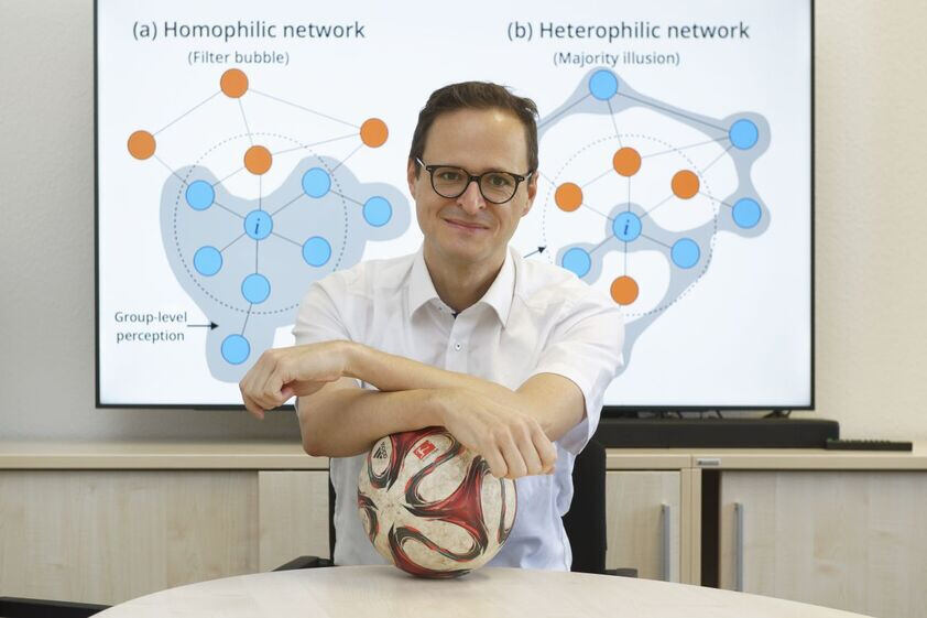 Professor Markus Strohmaier at his desk, leaning on a football
