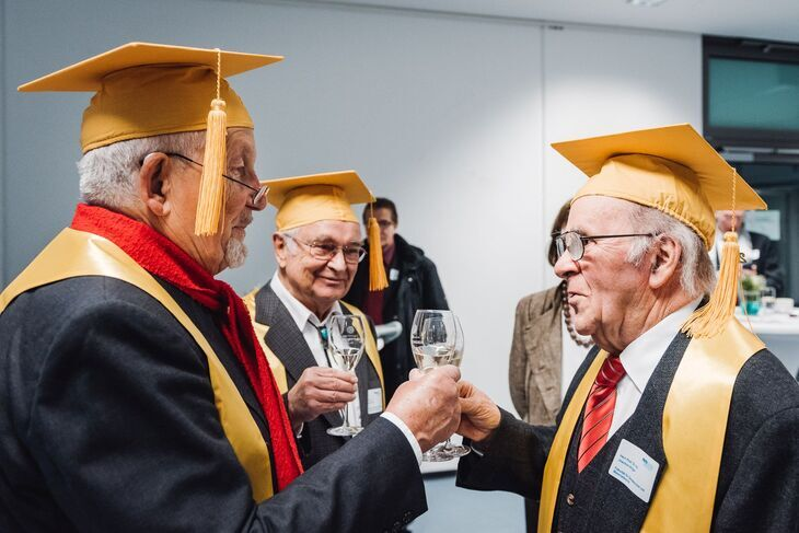 Three gold jubiliarians toasting each other