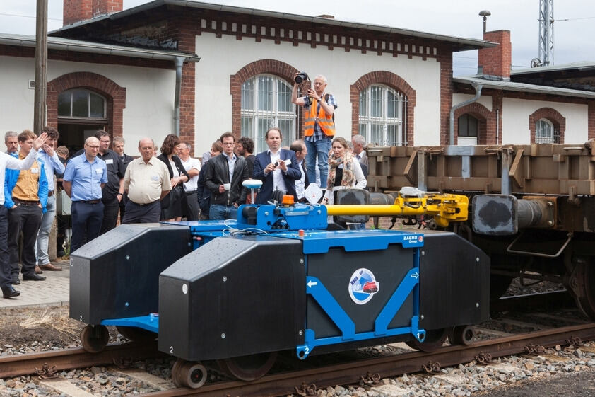Persons at a rail track looking at a demonstrator vehicle