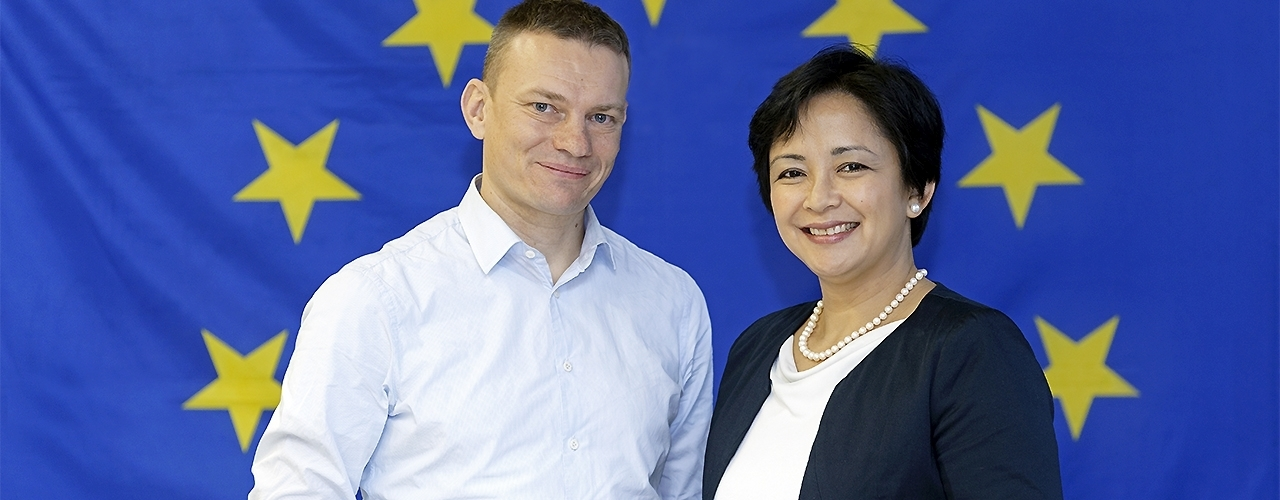 A woman and a man in front of the European flag