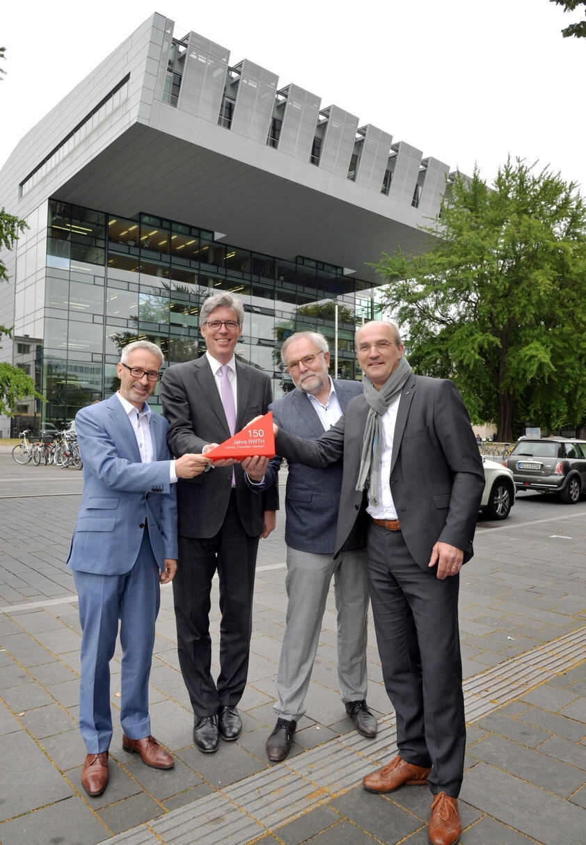 Four men holding a red pennant in front of the Super C building