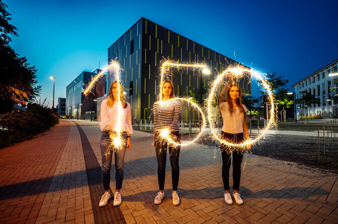 Three women forming the number 150 in the air with sparklers