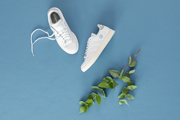 A pair of white sneakers featuring the RWTH monogram