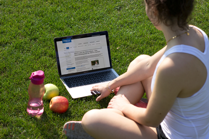 Student sitting outside on the grass with a notebook in front of her