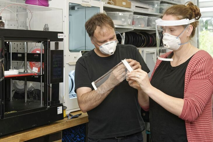 A man and a woman working on a face shield