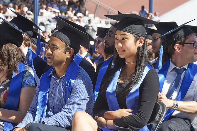 Young people sitting on chairs, wearing graduate caps