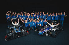 Group photo of Team Ecurie Aix with two students in front each sitting in a racing car